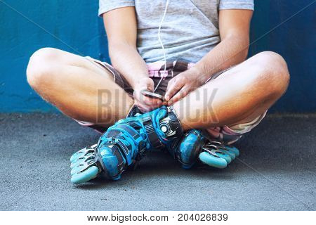Inline Roller Skater With Phone Sitting Against Blue Wall.