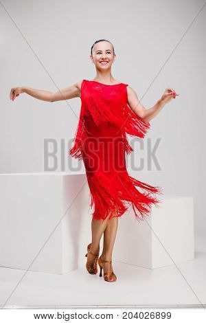 passionate girl in red dress dancing in studio, young woman posing while standing in a white studio