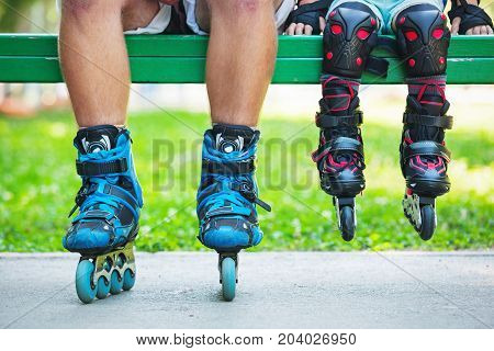 Close up photo of legs in inline skates sitting on bench. Learning skating concept image.