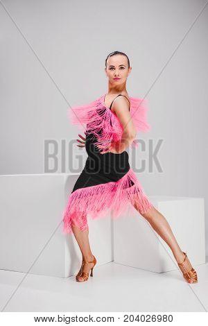 passionate woman in pink and black dress dancing in studio, woman posing sitting