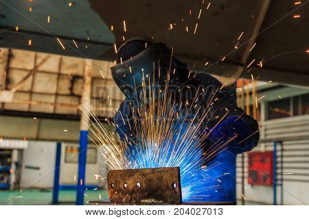 Lighting and hot sparks from worker is welding steel with welding gloves in car factory
