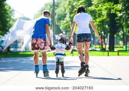 Cute Baby Boy And His Mom Learning Inline Skating With Skating Instructor.