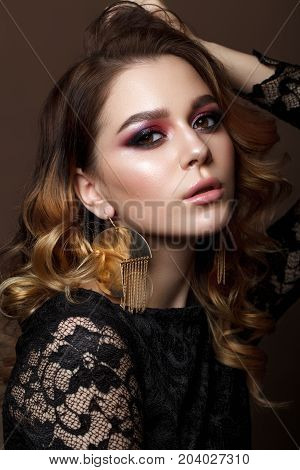 Beautiful young woman with evening makeup and wavy hairstyle. Purple smoky eyes