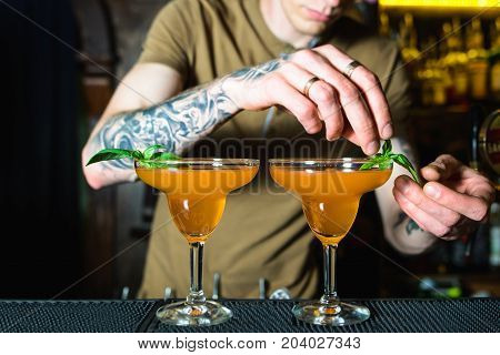 Barman is decorating cocktail.The barman creates a beautiful orange alcoholic cocktail.