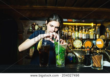 A woman bartender creates a nice alcoholic cocktail at the bar. The barman decorates mint cocktails. Bright alcoholic beverage