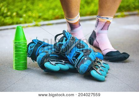 Blue Roller Skates With Slalom Cones And Roller Socks On Male Legs.