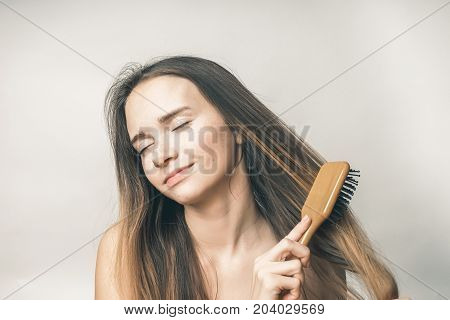 The girl combs her hair and enjoys it. Healthy and beautiful hair without problems
