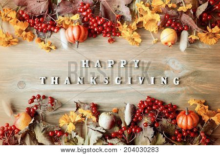 Thanksgiving day autumn background with Happy Thanksgiving letters, seasonal autumn nature berries, pumpkins, apples and flowers on the wooden background. Happy Thanksgiving concept. Holiday Thanksgiving background.Still life with Thanksgiving concept