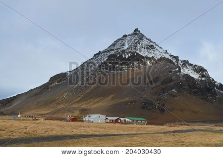 Farm houses located at the base of Mount Stapafell in iceland.