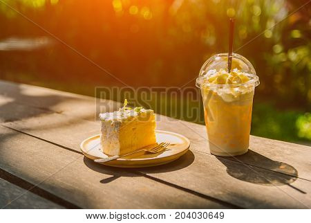 Coconut cake iced milk with caramel syrup and whipped cream l on wooden table in garden