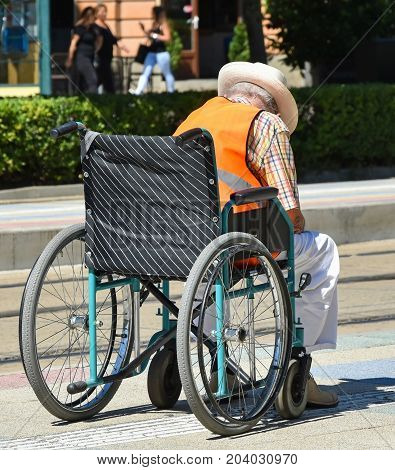 Old man in a wheelchair on the street