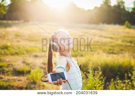 Joyful girl listening music with headphones and smiling friendly, cheerful child listening music on nature