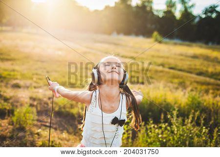 Pretty girl listening music with headphones and spinning, amusing child listening music and dancing