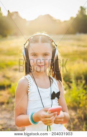 Joyful girl using mobile telephone and listenning music, cute child holding mobile and listenning music