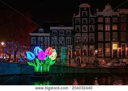 Amsterdam Netherlands - January 5 2017: Coloured tulips of light float on a canal during the Festival of Light in Amsterdam