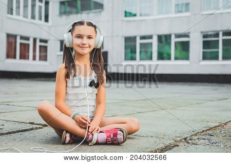 Pretty girl sitting and listening music with headphones, Little girl in a light sweater with a black bow listening to music on headphones