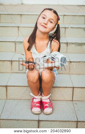 Little girl sitting on upstairs and holding white and black headphones. pretty little kid wearing on red sandals and white blouse