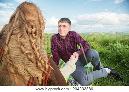 Young couple on a picnic in a beautiful place under the open sky. Sitting on a rug a guy looks at his lover against the background of green meadows and clouds