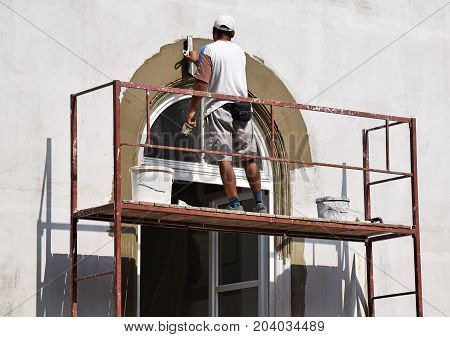 Construction worker works on the restoration of a building