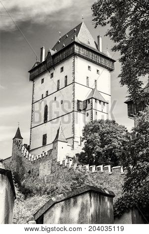 Karlstejn is a large gothic castle founded 1348 by Charles IV in Czech republic. Ancient architecture. Travel destination. Black and white photo.