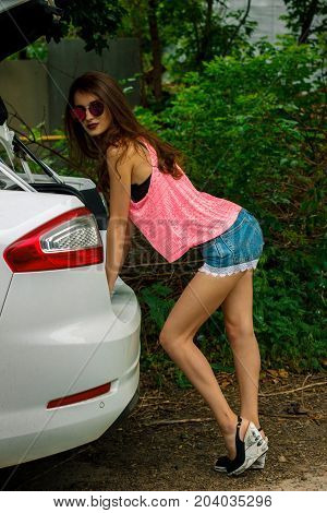 beautiful slender Lady in a pink t-shirt and denim shorts leaned to the car