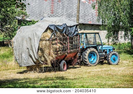 Old tractor with hay. Agricultural scene. Seasonal rural scene.