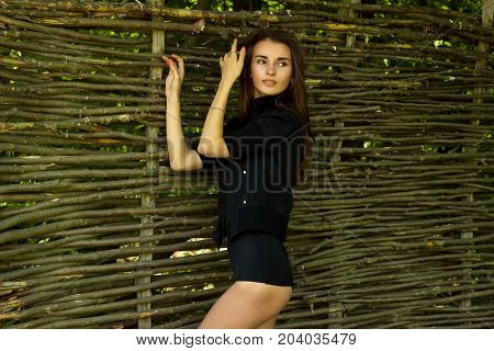 beautiful skinny brunette in black clothes standing near wooden wall