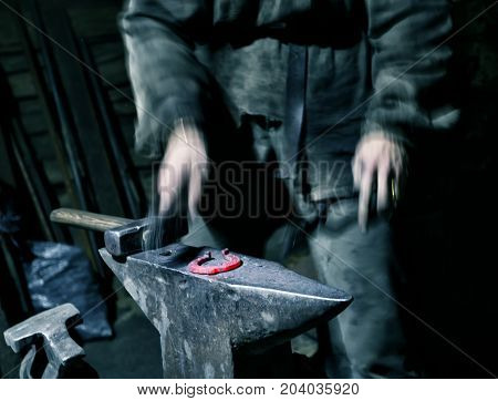 Hands of a blacksmith with a hammer blowing a warmed horseshoe. The concept of manual labor and the creation of a new product.