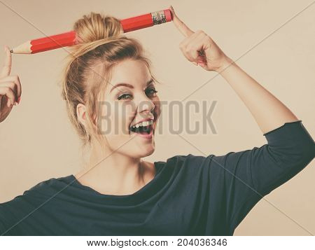 Charming happy blonde woman having big pencil in hair having fun education ideas.