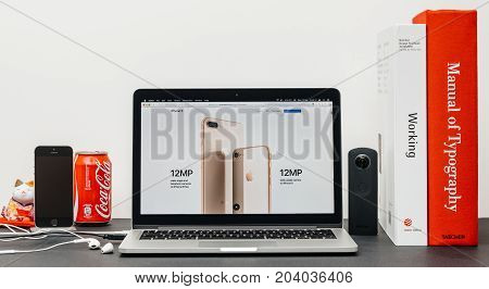 PARIS FRANCE - SEP 13 2017: Minimalist creative room table with Safari Browser open on MacBook Pro laptop showcasing Apple Computers website with latest iPhone 8 and 8 Plus with 12mp cameras