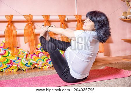 Pregnancy Yoga and Fitness concept. Healthy maternity lifestyle concept. Happy smiling 40 week pregnant middle aged caucasian woman doing yoga exercises sitting holding her legs up.