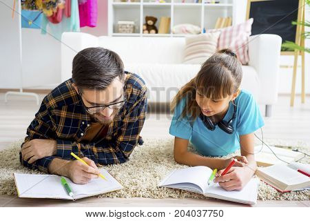 Father and his teenage daughter reading a book