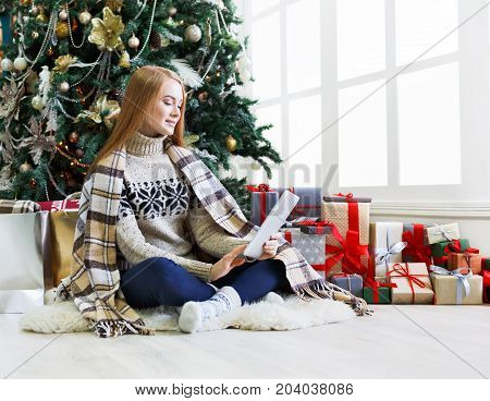 Christmas online shopping. Female buyer choosing presents on digital tablet sitting at decorated fir tree background among gift boxes and packages. Winter sales, copy space
