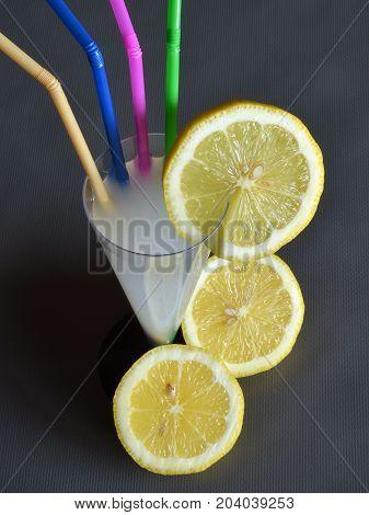 Drink a lemonade A lemonade inside a glass-shaped glass, beside a lemon cut into two parts