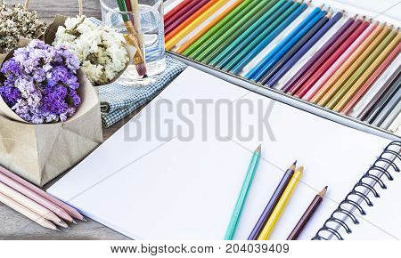 Colorful Color pencils for art drawing.Notebook of blank pages with paintbrush in glass and flower bouquet on wooden table background.