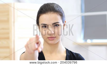 Woman Pointing Toward Camera In Office At Work
