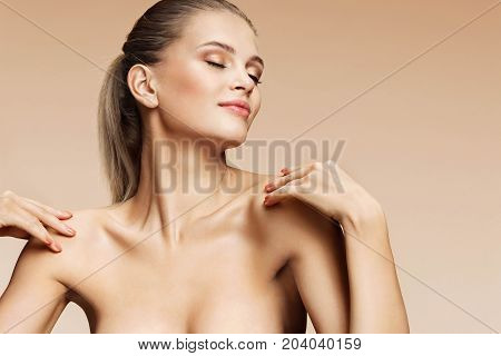 Sensual young woman touching her perfect skin. Photo of sexy woman with beautiful makeup on beige background. Beauty & Skin care concept
