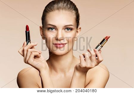 Beautiful young woman with lipstick. Portrait of woman with red and beige pomade on beige background. Youth and skin care concept