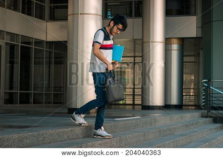young slim lad is standing on the street with a book under his arm and a bag