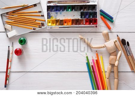 Workplace of artist. Paints and wooden painter man with brushes on white desk, top view, flat lay, objects