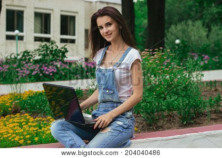beautiful tender woman sits on a street near the flowerbeds with a laptop in hand and smiling