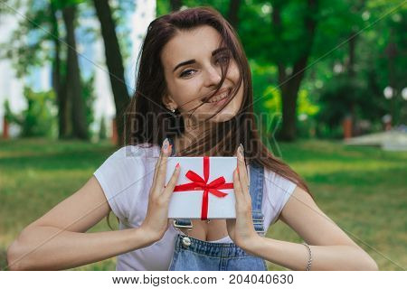 a close-up portrait of joyous beautiful brunette which holds the gift and looks into the camera in the street