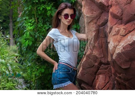 Portrait of sexual attractive brunette in sunglasses and jeans shorts