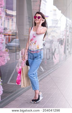 the charming slender women walking down the street with packages from stores