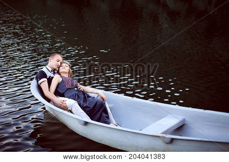 happy boyfriend and girlfriend resting on river, honey teenager enjoy nice weekend on lake, pretty girl and handsome guy hugging on white boat