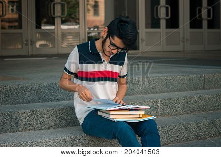 horizontal portrait of a young handsome guy with books on the street