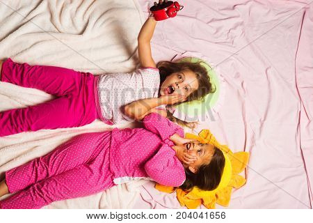 Children With Shocked Faces Lie On Pink Background Hold Clock