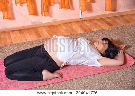 Pregnancy Yoga and Fitness concept. Healthy maternity lifestyle concept. 40 week pregnant middle aged caucasian woman doing yoga exercises laying leaning back.
