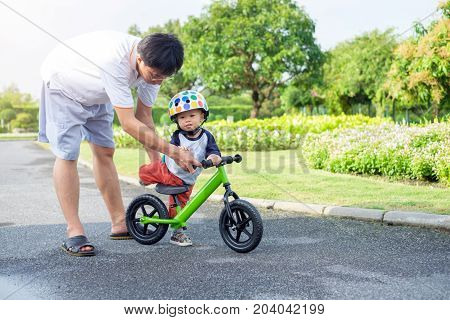 Young father spend time with Cute little Asian 18 months / 1 year old toddler boy child Dad and son play and have fun with balance bike (run bike) Dad tech son to ride bike father's day concept