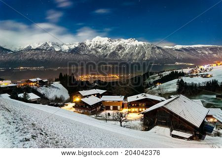Snowy landscape with traditional village at the Austrian Alps under the moonlight in winter